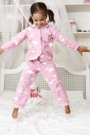 brincando: Chica joven que desgasta los pijamas que salta en cama Foto de archivo