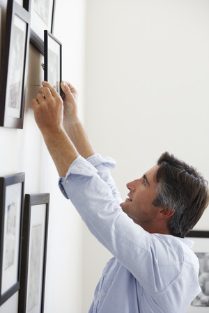 frame wall: Man Hanging Picture Frames On Wall At Home