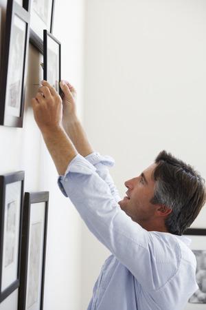 Man Opknoping Foto frames op muur thuis Stockfoto