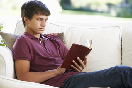 Teenage Boy Relaxing On Sofa At Home Reading Book