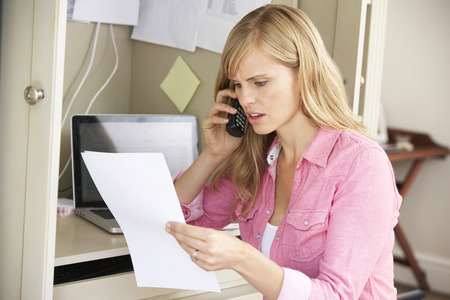 Woman Working In Home Office On Phone Standard-Bild