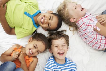 niños riendose: Vista desde arriba de cuatro niños jugando en la cama juntos