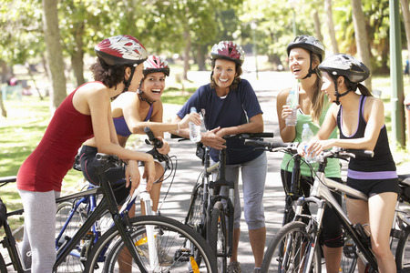 andando en bicicleta: Grupo de Mujeres de descanso Durante paseo del ciclo a trav�s de parque Foto de archivo