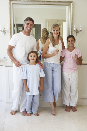 hygeine: Portrait Of Family About To Brush Teeth In Bathroom Mirror