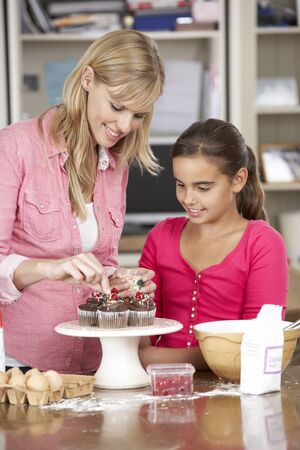 home decorating: Mother And Daughter Decorating Homemade Cupcakes In Kitchen Stock Photo