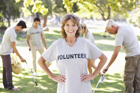 mixed race woman: Volunteer Group Clearing Litter In Park Stock Photo