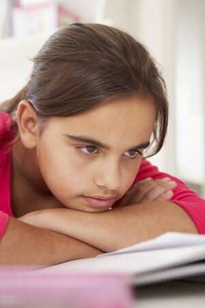 struggling: Bored Young Girl Doing Homework At Desk In Bedroom Stock Photo