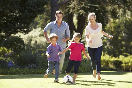 niños jugando en el parque: Familia que juega al balompié en jardín junto Foto de archivo