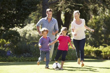 women playing soccer: Family Playing Football In Garden Together