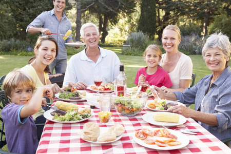 Three Generation Family Enjoying Barbeque In Garden Together Stockfoto