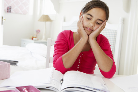 10 year old: Bored Young Girl Doing Homework At Desk In Bedroom Stock Photo