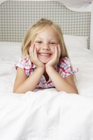 girl lying: Young Girl Lying On Bed Smiling