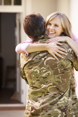 returning: Soldier Returning Home And Greeted By Wife Stock Photo