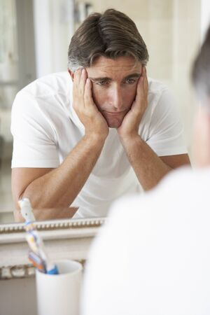 the ageing process: Unhappy Man Looking At Reflection In Bathroom Mirror Stock Photo