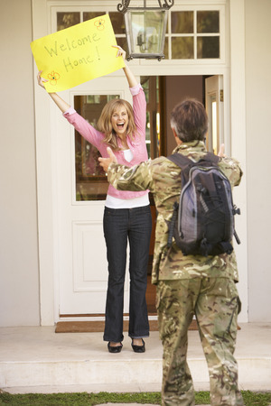 homecoming: Soldier Returning Home And Greeted By Wife Stock Photo