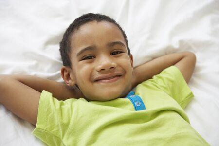 niños riendose: Young Boys relax en la cama Foto de archivo