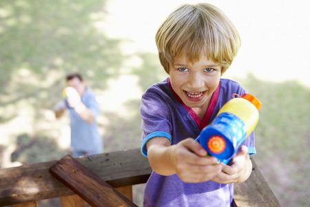 아버지와 아들 나무 집에서 물 권총 싸움을 갖는 스톡 콘텐츠 - 42247938