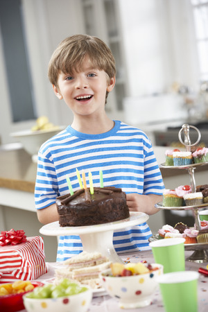 party with food: Young Boy Standing By Table Laid With Birthday Party Food