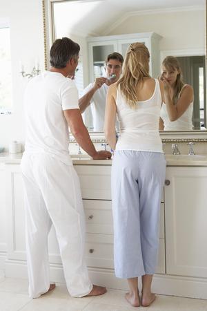 hygeine: Couple Brushing Teeth In Bathroom Mirror