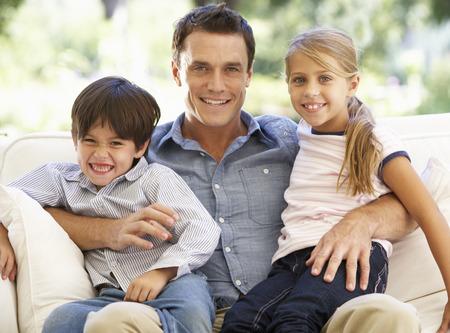 padre e hija: Padre y niños que sentado en el sofá en casa Foto de archivo