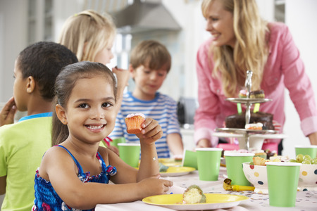 party with food: Group Of Children Enjoying Birthday Party Food At Table Stock Photo