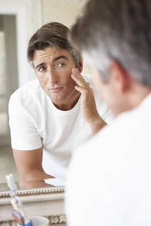 the ageing process: Man Looking At Reflection In Bathroom Mirror Stock Photo