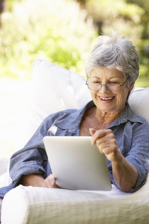 technology people: Portrait Of Senior Woman Using Digital Tablet At Home
