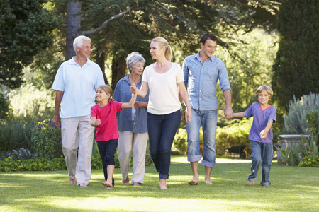 Tři generace rodiny procházky v zahradě spolu
