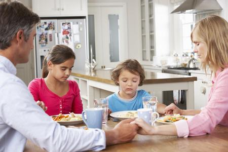 family praying: Familia Orando antes de tener la comida en cocina Juntos