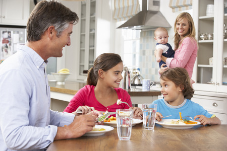 5 10 year old girl: Family Having Meal In Kitchen Together
