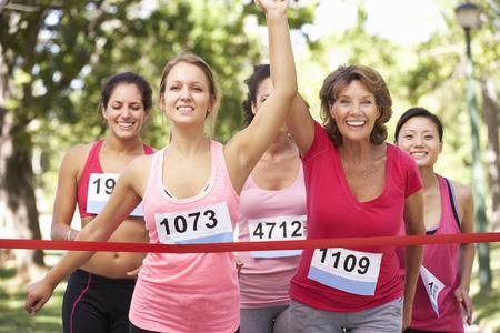 チャリティー マラソンを完了する女性選手のグループ