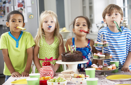 children birthday: Group Of Children Standing By Table Laid With Birthday Party Food