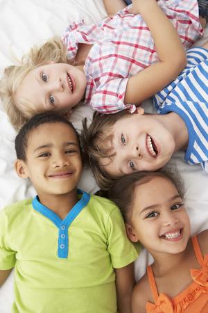 Vista desde arriba de cuatro niños jugando en la cama juntos