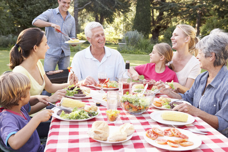 Three Generation Family Enjoying Barbeque In Garden Together Stock fotó