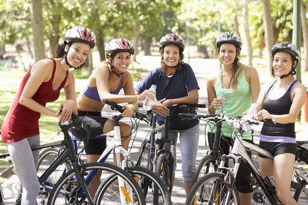 andando en bicicleta: Grupo de Mujeres de descanso Durante paseo del ciclo a través de parque Foto de archivo