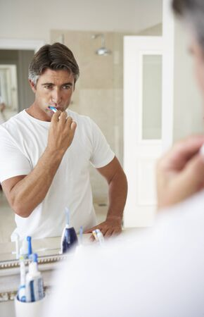 hygeine: Man Brushing Teeth In Bathroom Mirror