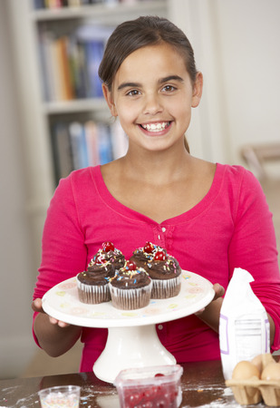 10 year old: Girl With Homemade Cupcakes In Kitchen