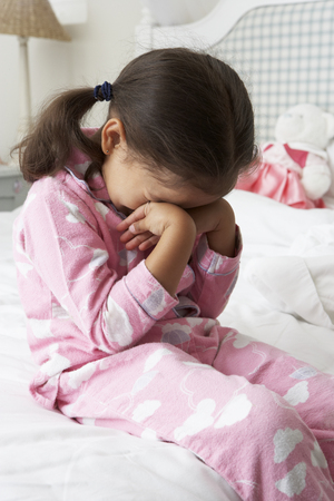 young female: Tired Young Girl Wearing Pajamas Sitting On Bed Stock Photo