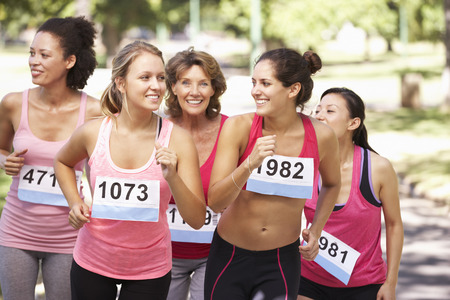 Group Of Female Athletes Competing In Charity Marathon Race 스톡 콘텐츠