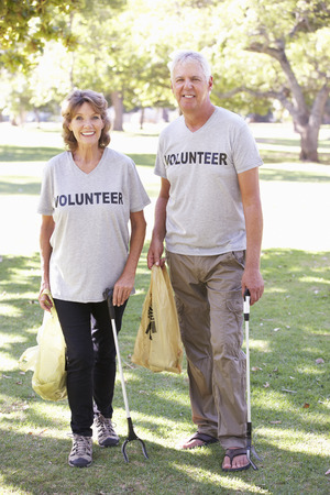 volunteer: Senior Couple Working As Part Of Volunteer Group Clearing Litter In Park Stock Photo