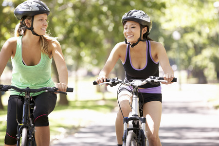asian lady: Two Women Cycling Through Park Stock Photo