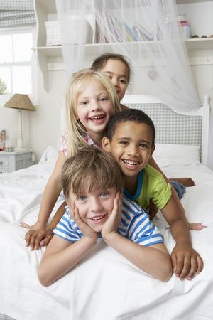 niños jugando: Cuatro Niños Jugando En La Cama Juntos