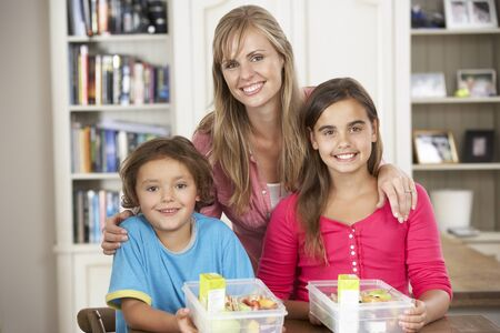 5 10 year old girl: Mother Giving Two Children Healthy Lunchboxes In Kitchen