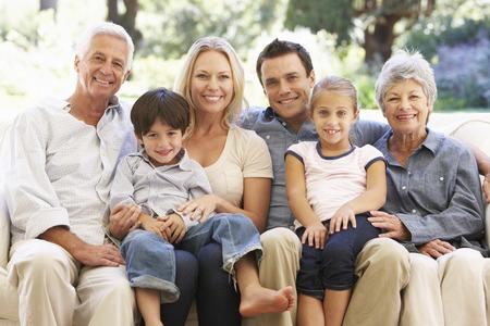 ancianos felices: Familia de tres generaciones que se sienta en el sofá en casa