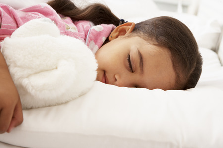 cuddly toy: Young Girl Asleep In Bed With Cuddly Toy Stock Photo
