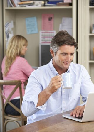 home working: Couple Working In Home Office Together