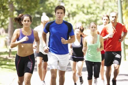 hacer footing: Grupo de los corredores de jogging a través de parque