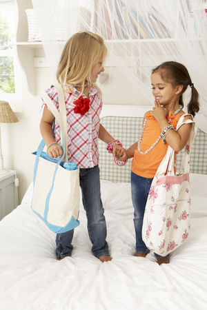 dressing up: Two Young Girls Dressing Up Together In Bedroom