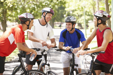 50s man: Group Of Men Resting During Cycle Ride Through Park Stock Photo