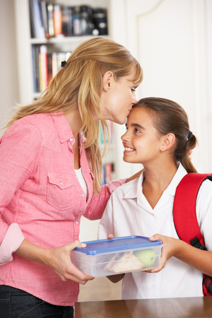 Mother Giving Daughter Healthy Lunchbox In Kitchen Stock Photo